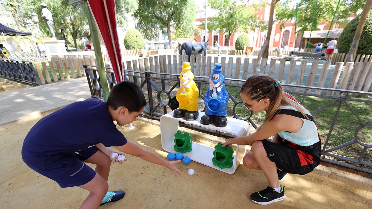 Los Ninos Disfrutan En El Prado De Juegos De Punteria Y Golosinas